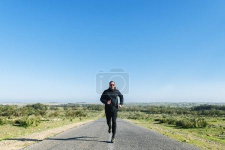 Runner man athlete running on road.