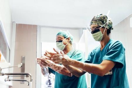 Photo pour Deux chirurgiens se lavent les mains avant d'opérer. Concept hospitalier . - image libre de droit