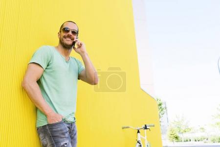 Handsome young man with mobile phone and fixed gear bicycle.