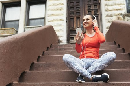 Beautiful woman using phone after running.