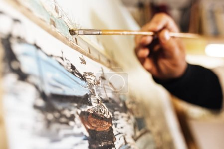 Close up of man artist painting oils in his studio.