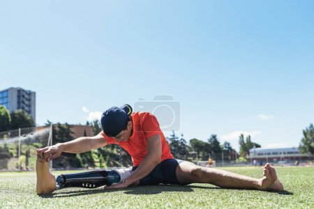 Photo for Disabled man athlete stretching with leg prosthesis. Paralympic Sport Concept. - Royalty Free Image