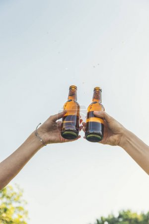 Photo for Female friends cheers clinking bottles of beer in hands in the park. - Royalty Free Image