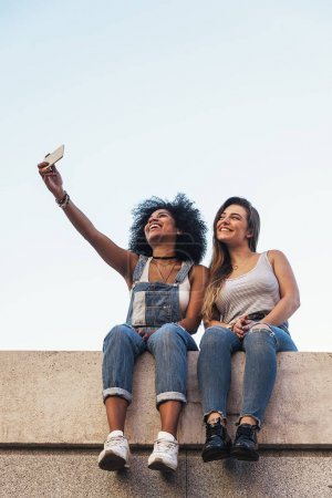 Beautiful women taking a self portrait in the Street.