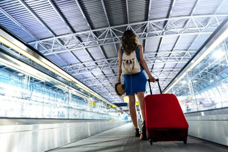 Young girl traveler walking with carrying hold suitcase in the a