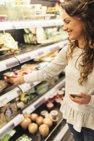 Beautiful woman choosing food in supermarket.