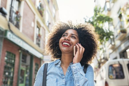 Beautiful afro american woman using her mobile in the street.