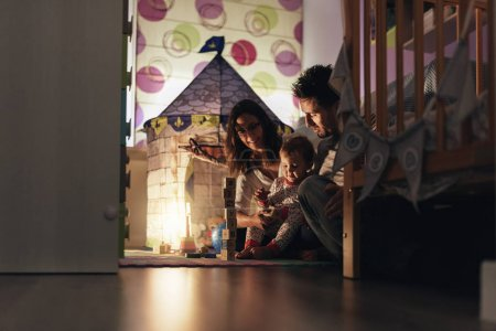 Parents enjoying playing with their son at home.