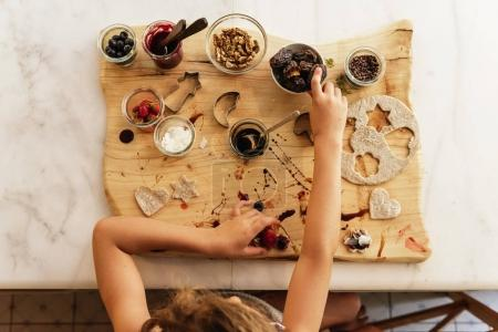 Top view of little girl preparing baking cookies.