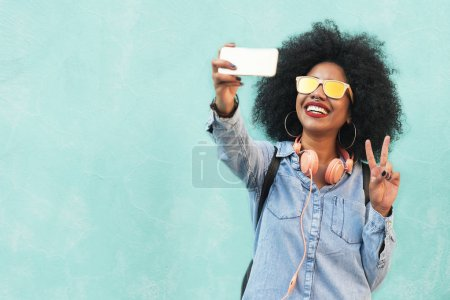 Self portrait of beautiful young afro american woman making peac