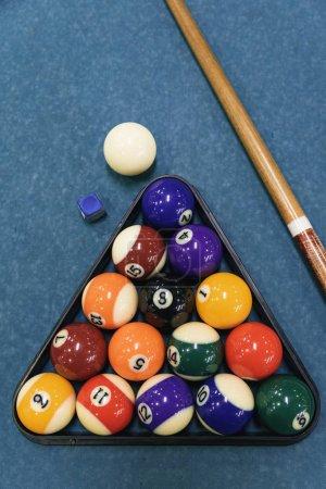 Billiard balls an cue on billiards table.