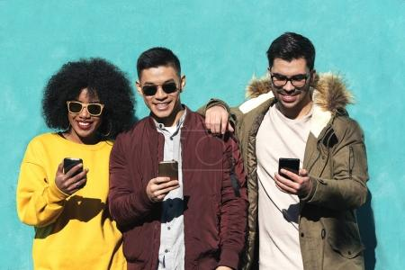 Photo for Group of happy friends using the mobile in the street. Friendship concept. - Royalty Free Image