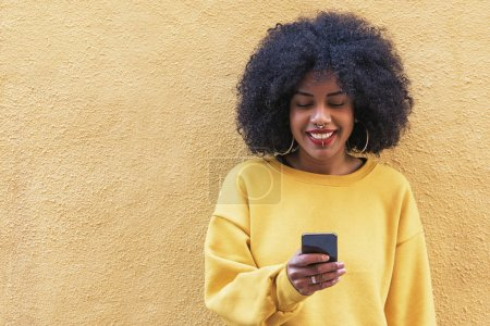 Beautiful afro american woman using mobile in the street.