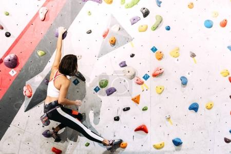 Photo for Woman practicing rock climbing on artificial wall indoors. Active lifestyle and bouldering concept. - Royalty Free Image