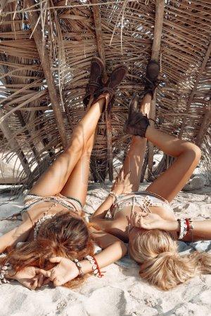 Photo pour Jolies jeunes femmes bohémiennes se posant ensemble sur une plage tropicale - image libre de droit