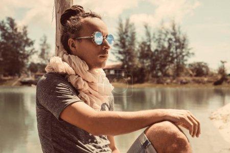 Photo pour Jeune homme attirant assis à l'extérieur au fond d'un lac - image libre de droit
