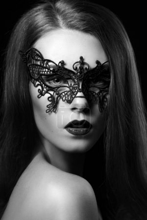 portrait of mysterious woman in lace mask on black background