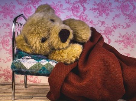 Enfermo oso de peluche acostado en la cama solo .