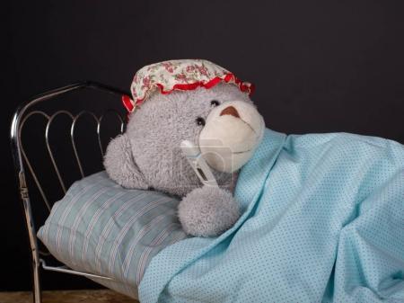 oso de peluche enfermo acostado en la cama con una temperatura .