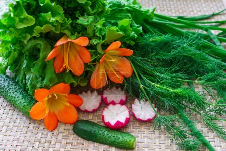 Fresh cucumber, sliced radish, greens and flowers of the clivia for decoration.