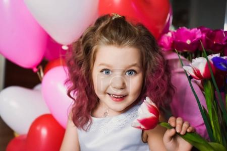 Little beautiful girl with pink curly hair in a silver dress in red tulips and with multi-colored balls