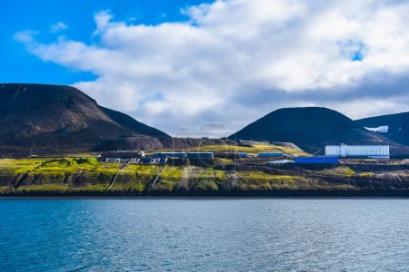 Landscape of the Russian  city of Barentsburg on the Spitsbergen archipelago in the summer in the Arctic In sunny weather and blue sky