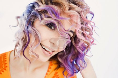 close-up portrait in studio isolated beautiful sexy young blond hipster girl with lilac and pink hair posing with tooth smile
