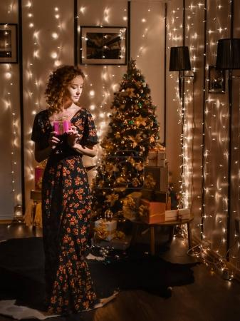 Photo for Portrait of beautiful young sexy curly red-haired girl on background merry christmas happy new year tree lights with star gift decor - Royalty Free Image