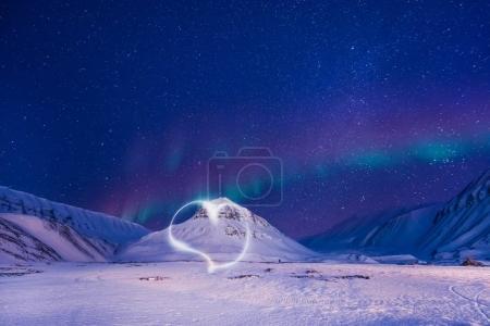 The polar arctic Northern lights aurora borealis sky star in Norway Svalbard in Longyearbyen city man mountains