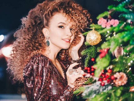 Photo for Portrait of beautiful young  curly girl on background merry Christmas happy new year tree lights with star disco decor - Royalty Free Image