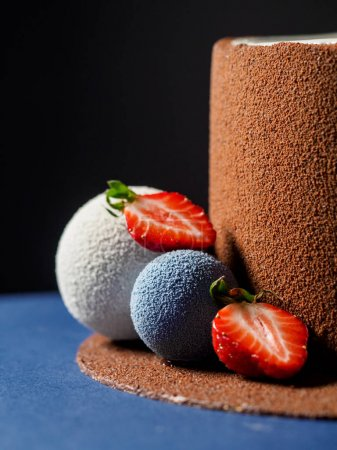 cake covered with chocolate velvet and decorated with chocolate spheres close up.  vertical photo, dark background, right side composition