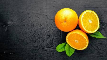 Photo for Fresh citrus fruits. Orange. On a black background Wooden. Top view. - Royalty Free Image