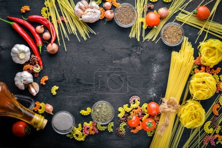 Photo for Pasta with vegetables, cherry tomatoes, chili peppers and garlic. On a wooden background. Free space for text . Top view - Royalty Free Image