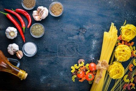 Photo pour Pâtes avec légumes, tomates cerises, piments et ail. Sur un fond en bois. Espace libre pour le texte. Vue du dessus - image libre de droit