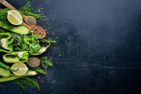 Photo pour Un large choix de légumes verts et d'épices sur fond de bois. Vue de dessus. Espace libre . - image libre de droit