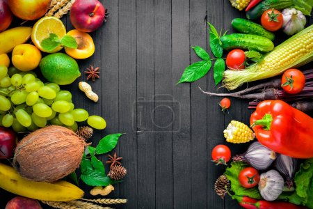 Photo for Large selection of raw vegetables and fruits on a black wooden table. Free space for your text. Top view. - Royalty Free Image