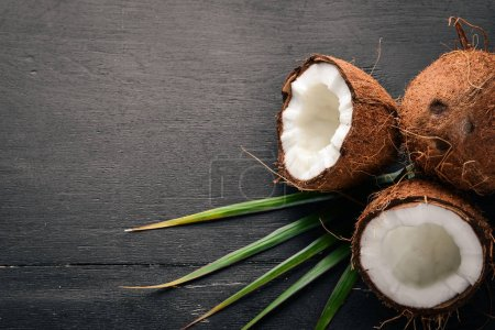Coconut on a wooden background. Tropical fruits and nuts. Top view. Free space for text.