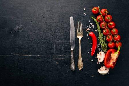 Photo pour Préparation à la cuisson. Tomates cerises. Légumes frais et épices sur fond de bois. Vue du dessus - image libre de droit