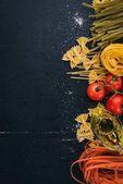 """Постер, картина, фотообои """"Набор макароны, лапша, спагетти, Тальятелле, Фетучини Фарфалле. Блюда итальянской кухни, свежие овощи и специи. На черном фоне, деревянные. Вид сверху. Копией пространства."""""""