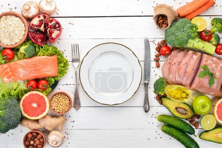 Photo for Healthy food background. Concept of Healthy Food, Chicken Fillet, Raw Meat, Fish, Avocado, Broccoli, Fresh Vegetables, Nuts and Fruits. On a wooden background. Top view. Copy space. - Royalty Free Image