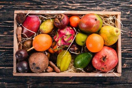 Photo pour Fruits tropicaux dans un coffret en bois. Papaye, Fruit du Dragon, ramboutan, tamarin, fruit du cactus, avocat, granadilla, carambole, kumquat, mangue, mangoustan, fruit de la passion, noix de coco. - image libre de droit