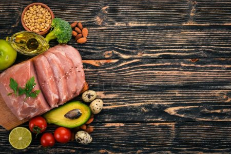 Photo for Healthy food. Raw meat, avocado, broccoli, fresh vegetables, nuts and fruits. On a wooden background. Top view. Copy space. - Royalty Free Image