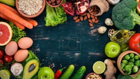 Photo for Healthy food background. Concept of Healthy Food, Fresh Vegetables, Nuts and Fruits. On a wooden background. Top view. Copy space. - Royalty Free Image