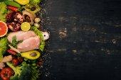 """Постер, картина, фотообои """"Здоровая пища. Куриное филе, авокадо, брокколи, свежие овощи, орехи и фрукты. На фоне деревянные. Вид сверху. Копией пространства"""""""