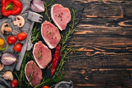 Photo pour Viande crue. Steak de boeuf avec romarin et épices sur fond de bois noir. Vue de dessus. Espace libre pour le texte . - image libre de droit