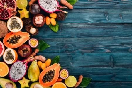 Photo for Tropical fruits, papaya, Dragon Fruit, rambutan, tamarind, cactus fruit, avocado, granadilla, carambola, kumquat, mango, mangosteen, passionfruit, coconut. On a wooden background. - Royalty Free Image