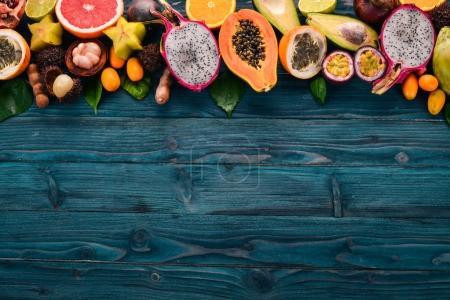 Photo pour Fruits tropicaux, papaye, Dragon Fruit, rambutan, tamarin, cactus, avocat, granadille, carambole, kumquat, mangue, mangoustan, fruit de la passion, noix de coco. Sur un fond en bois . - image libre de droit