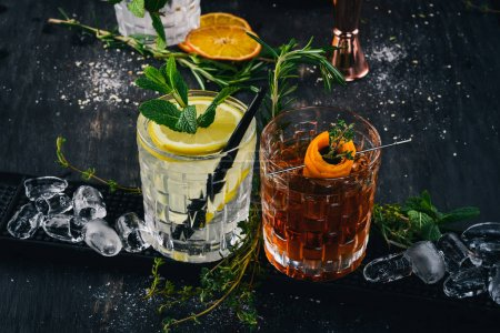 Photo for Two Alcoholic Cocktail Gin and Tonic, Negroni. On a black wooden background. - Royalty Free Image