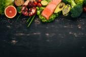 """Постер, картина, фотообои """"Здоровая пища. Рыба, лосось, авокадо, брокколи, свежие овощи, орехи и фрукты. На черном фоне. Вид сверху. Копией пространства."""""""