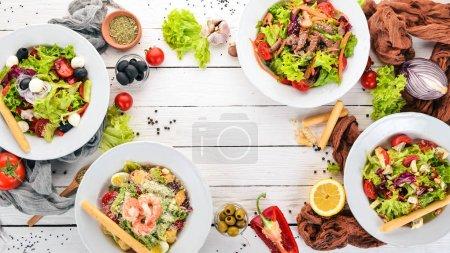 Photo pour Assortiment de salades de légumes frais. Une nourriture saine. Sur un fond de bois blanc. Vue de dessus. Copiez l'espace pour votre texte . - image libre de droit